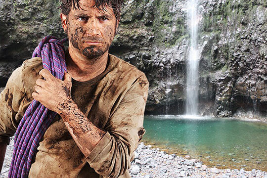man covered in mud and dirt standing in front of a waterfall