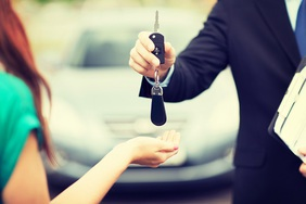 Car salesman handing keys to driver