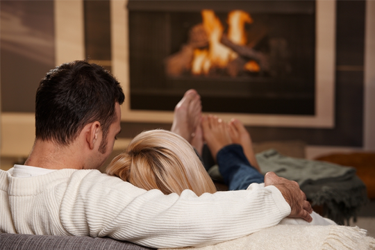 Couple sat in front of a fireplace