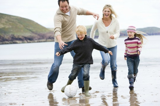 A family running on the beach on a dreary day kicking a football